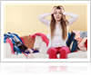 Confused woman sitting on sofa full of clothes
